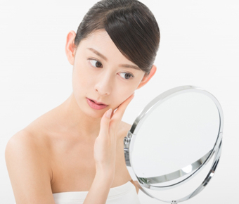 鏡で肌の状態を確認している女性